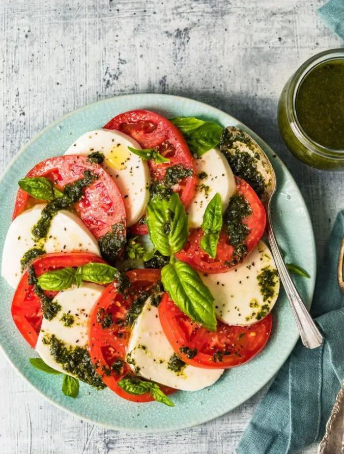 Яркий летний салат из помидор и сыра моцарелла с зеленью на тарелке