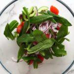 В миске листья мяты, зелень и овощи