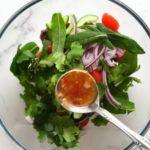 В миске зелень, овощи и ложка с острым соусом
