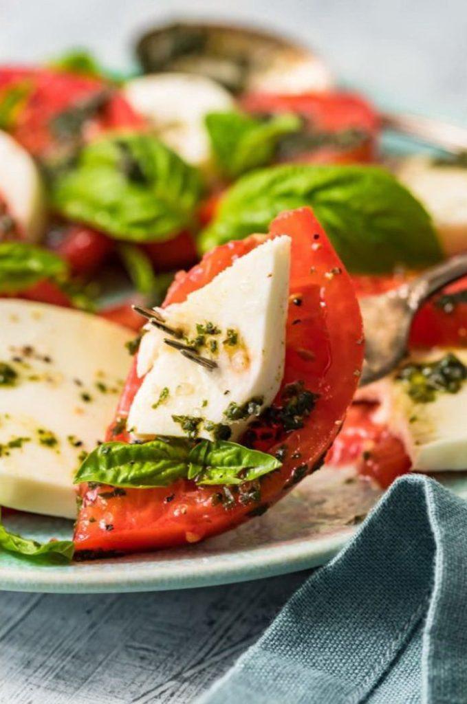 Кусочек сочного помидора, сыра и зелени на вилке