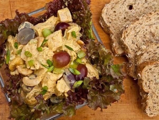 Салат с курицей, карри, кешью и виноградом на тарелке