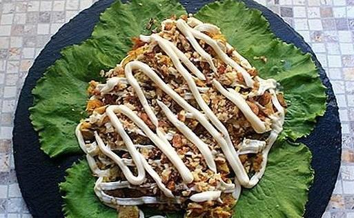 На тарелке листья салата, курица, орехи и майонез