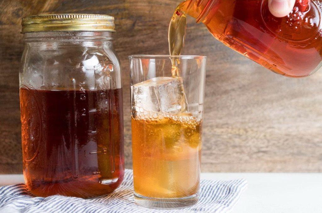 Наливают холодный чай латте в стакан с кубиками льда (пока без молока)
