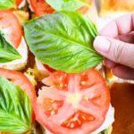 Листья базилика и помидоры на бутербродах