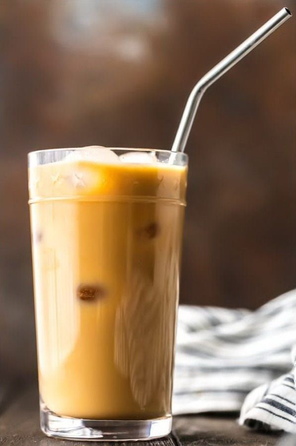 Холодный кофе со сливками в стакане с соломинкой