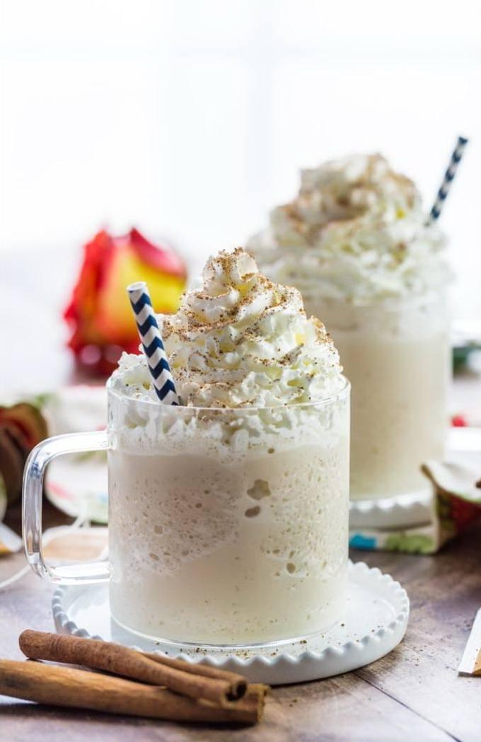 Две чашки с молочным коктейлем с чаем и мороженым, со взбитыми сливками
