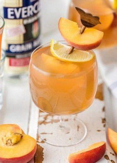 Коктейль на основе домашней водкой с персиками и чаем в бокале, украшенном палочкой с ломтиками персика и лимона