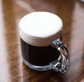 Стеклянная кружка с черным кофе и сливками