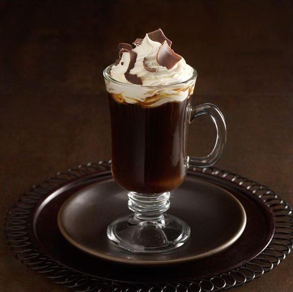 Стеклянная чашка на ножке с черным кофе и шапкой взбитых сливок с завитками шоколада