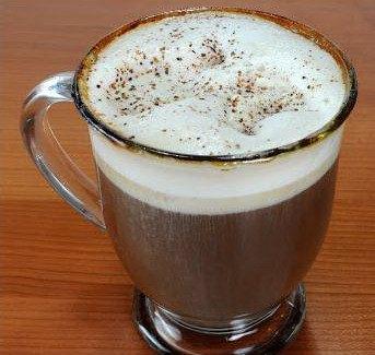 Стеклянная чашка кофе с ликерами, взбитыми сливками и орехами
