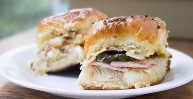 2 румяных сэндвича со свининой по-кубински на тарелке