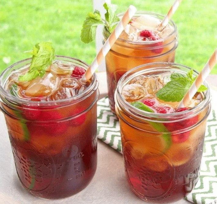 Освежающий чай с малиной, грейпфрутом, украшенный листьями мяты в красивых баночках с соломинками