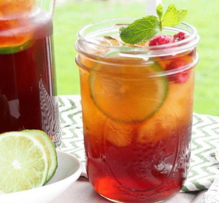 Стеклянная баночка с малиновым освежающим чаем с долькой грейпфрута, кубиками льда и листьями мяты