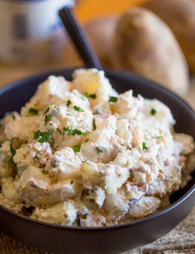 Салат из картофеля со сметаной и сыром, посыпанный зеленым луком в черной миске