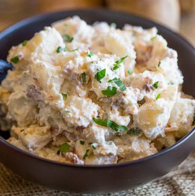 Салат из картошки со сметаной и сыром с зеленым луком в черной миске