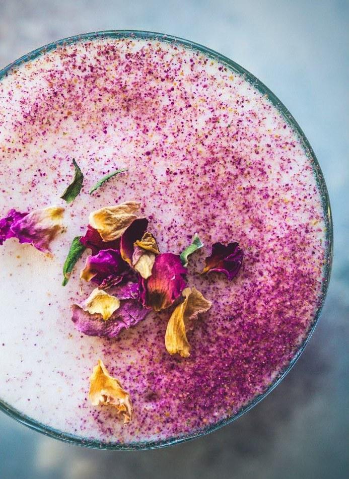 Стакан черного чая с бергамотом, с молочной шапкой, украшенной лепестками роз и розовой пылью, вид сверху