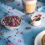 Чай с бергамотом, молоком и розовым сиропом в стакане и розовые лепестки в мисочке