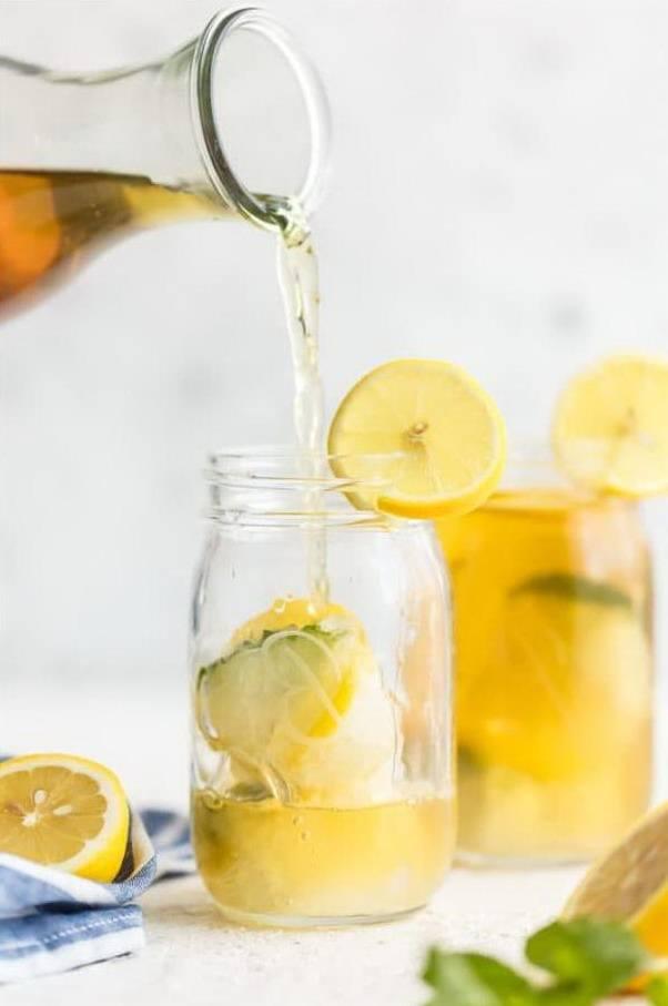 Из стеклянного кувшина наливают чай в баночку с лимоном и льдом