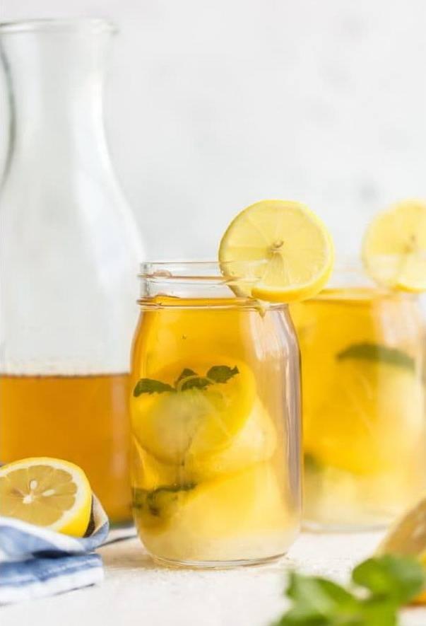 Стеклянный графин и баночки с чаем лимоном и кубиками льда