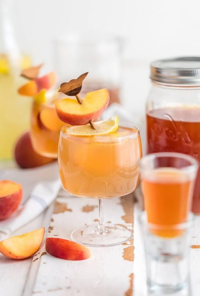 Коктейль на основе домашней водкой с персиками и чаем в бокале