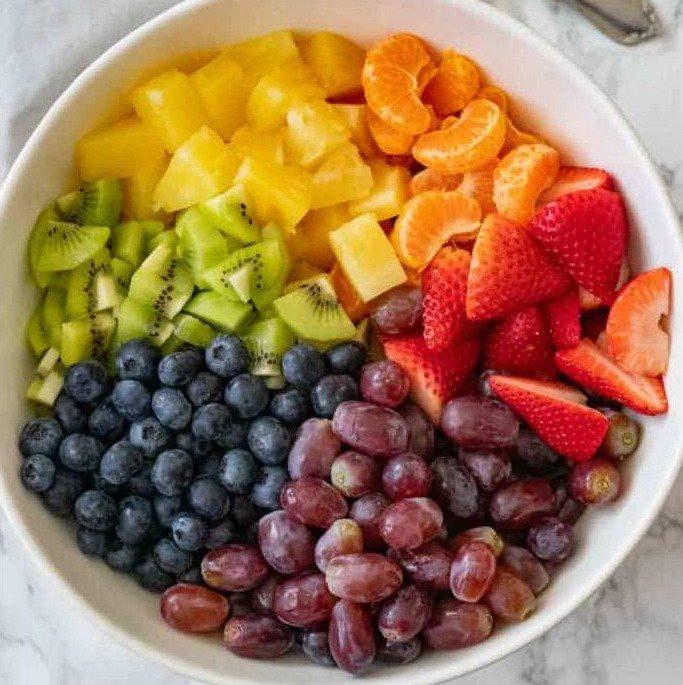 Нарезанные ингредиенты фруктового салата с ягодами и заправкой с медом
