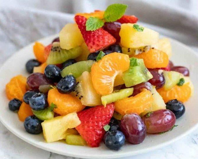 Фруктовый салат с ягодами и медом на тарелке
