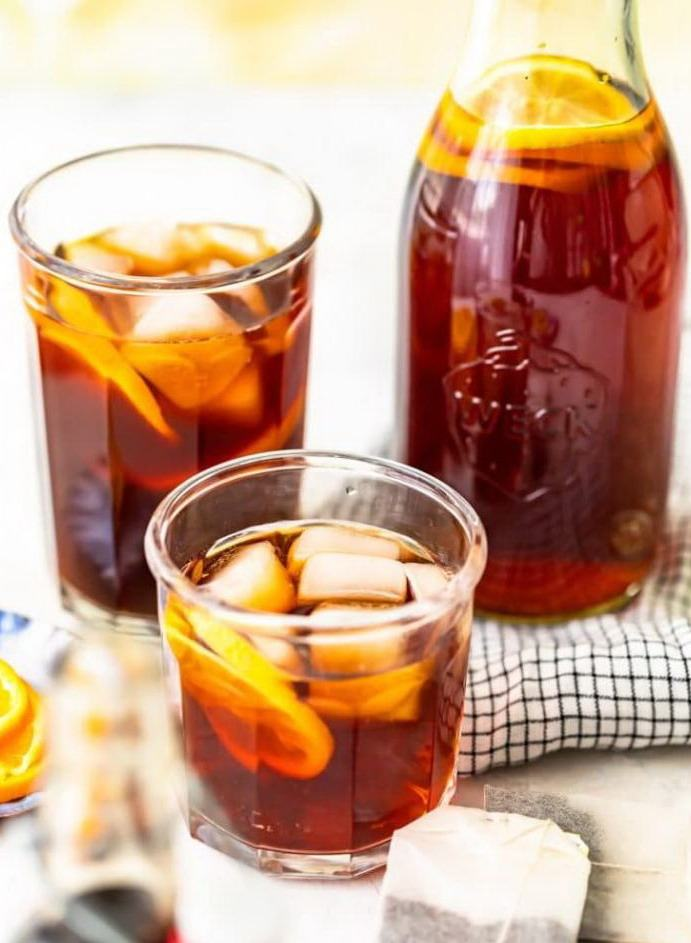 Чай с кубиками льда и дольками лимона в стаканах и кувшине