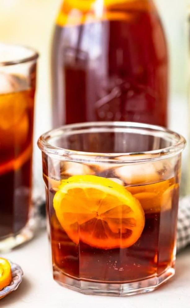 Чай с долькой лимона и кубиками льда в стакане