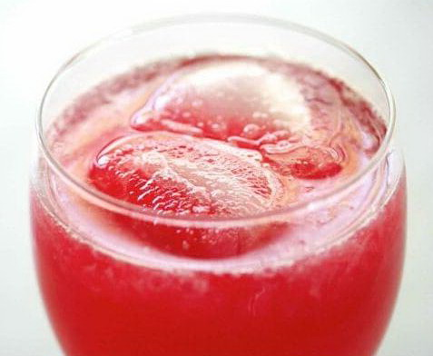 Розовый лимонад с клюквой и кубиками льда в стакане