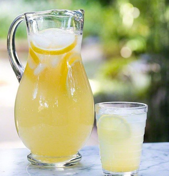 Домашний лимонад в кувшине и стакане с дольками лимона и кубиками льда