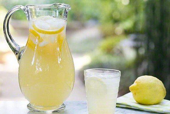 Лимонад в домашних условиях в стеклянном кувшине и стакане с лимоном и льдом
