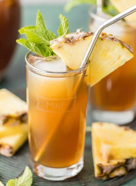 Ананасовій чай в стакане с трубочкой и льдом кубиками с кусочком ананаса