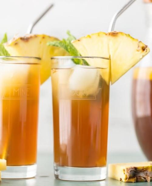 Чай с соком и кусочками ананаса в стаканах с мятой и кубиками льда